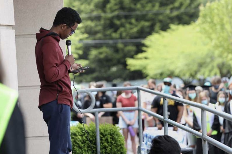 a teen leader holds a microphone as he speaks to a crowd of protestors at his high school