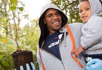 father holding his son and a sapling tree to be planted