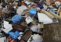Loads of mixed items including anything from baskets to fire pits to mattresses are unloaded into a giant heap.