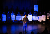 """Actors on stage recreating the March on Washington and Dr. Martin Luther King, Jr.'s """"I have a dream speech.""""  Actors hold signs that say """"freedom"""" """"we shall overcome"""" """"fight for our rights"""" and more."""