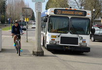 A bicyclist rides alongside a TriMet bus.