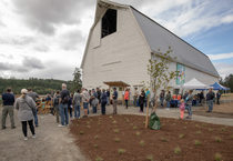 Visitors gather next to a restored dairy barn for the grand opening ceremony of Killin Wetlands Nature Park.