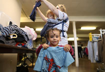 a little girl holds up a super hero shirt that she found in a clothing bin