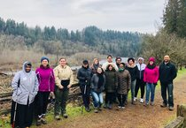 Group of 14 people standing on trail taking group photo with river and forest in background on cloudy winter day