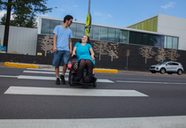 Young man and woman crossing street. Woman is using a mobility device