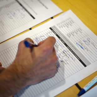 photo of someone adding their name to a sign-in sheet