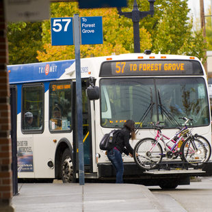 photo of woman loading a bike onto a bus