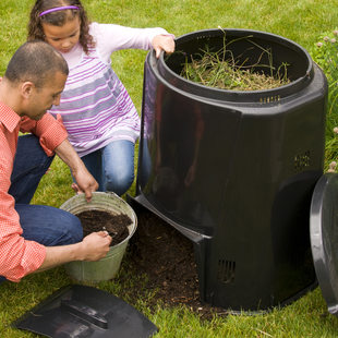photo of a dad and daughter filling a compost bin