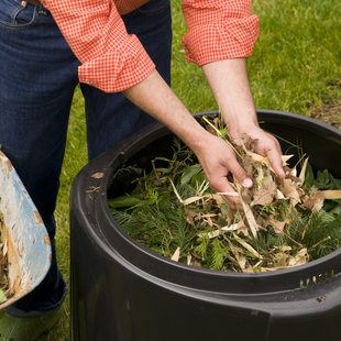 photo of a woman adding plant scraps to a compost bin