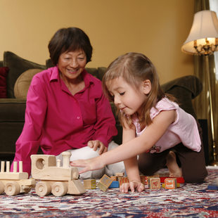 photo of a grandmother and child playing with a wooden train
