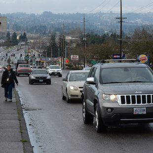 People walking and driving on Pacific Highway in Tigard