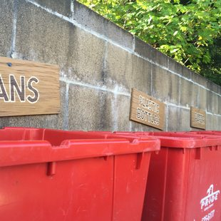 red recycling bins labeled for different materials