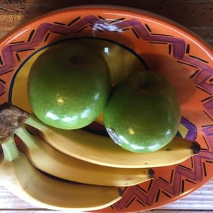 green apples and bananas in a bowl