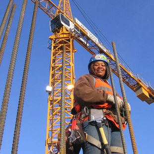 photo of construction worker and crane