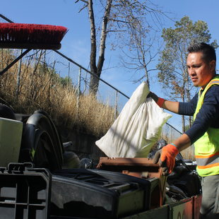 Photo of RID Patrol crew supervisor Juan Garcia loading truck with garbage