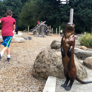 bronze sculpture of an otter and children playing at Nadaka Nature Park