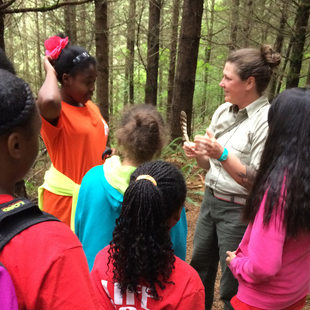 naturalist holding a feather and teaching kids at Oxbow Regional Park