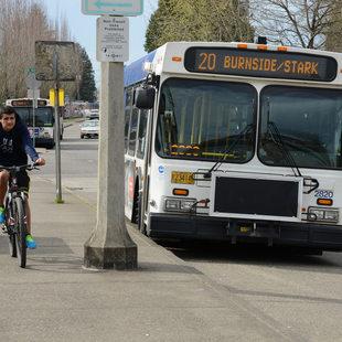 A bicyclist rides alongside a TriMet bus.