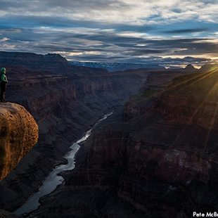 A person looks out over the Grand Canyon.