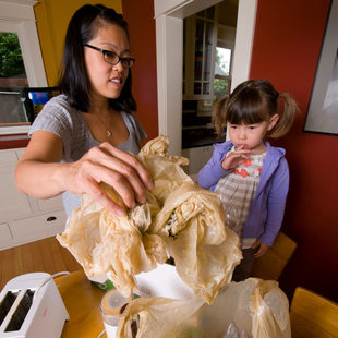 mother and daughter with plastic bags in the kitchen