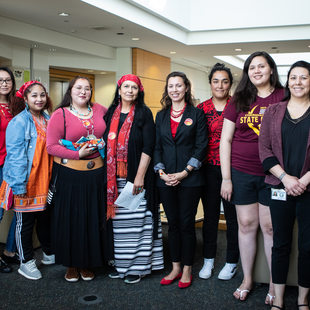 A group of Native American women stand side by side
