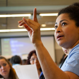 Woman raising her hand and speaking to a group