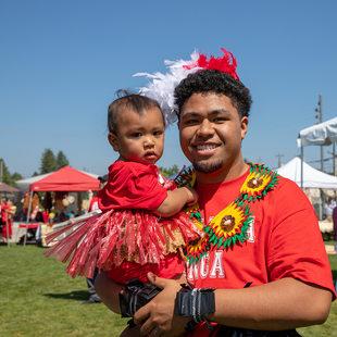 A young Tongan man holds a toddler