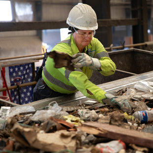 a woman in a hard hat sorts through garbage on a conveyor belt