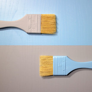 gray paintbrush on blue background above blue paintbrush on gray background