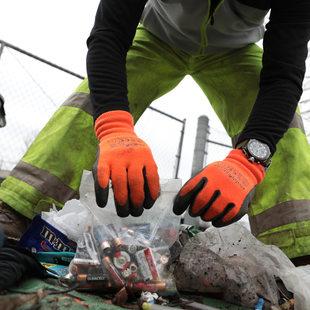 gloved hands put batteries into a ziplock bag