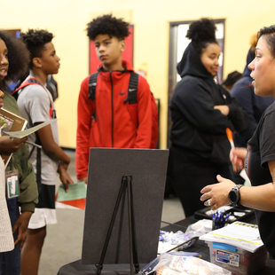 woman talking to students at SEI trades fair
