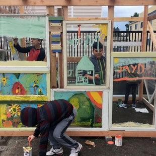 little boys working on an art installation in a backyard