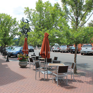 outside dining tables and other street furniture on the wide sidewalk alongside Avenue A in downtown Lake Oswego