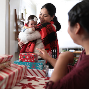 A multi-generational family gathers around holiday gifts