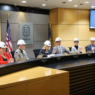 Metro Councilors sit at the chairs in Council Chambers wearing hard hats