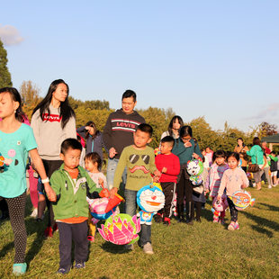 Asian families walking together in a park while holding lanterns
