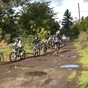 a group of middle school students and their chaperones bike down an unpaved street
