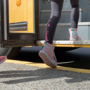 the feet of school children boarding a bus