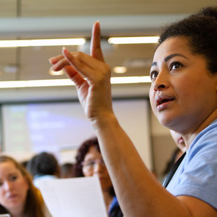 A woman raises her hand during a community forum