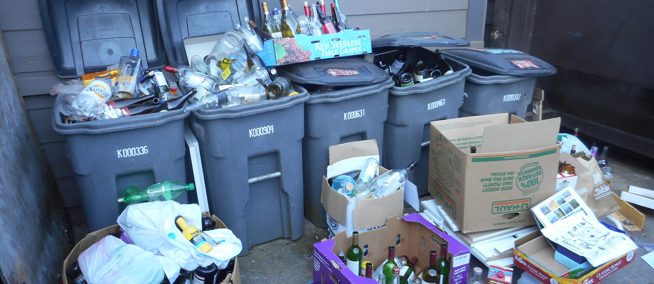 grey recycling bins overflowing with materials to be recycled