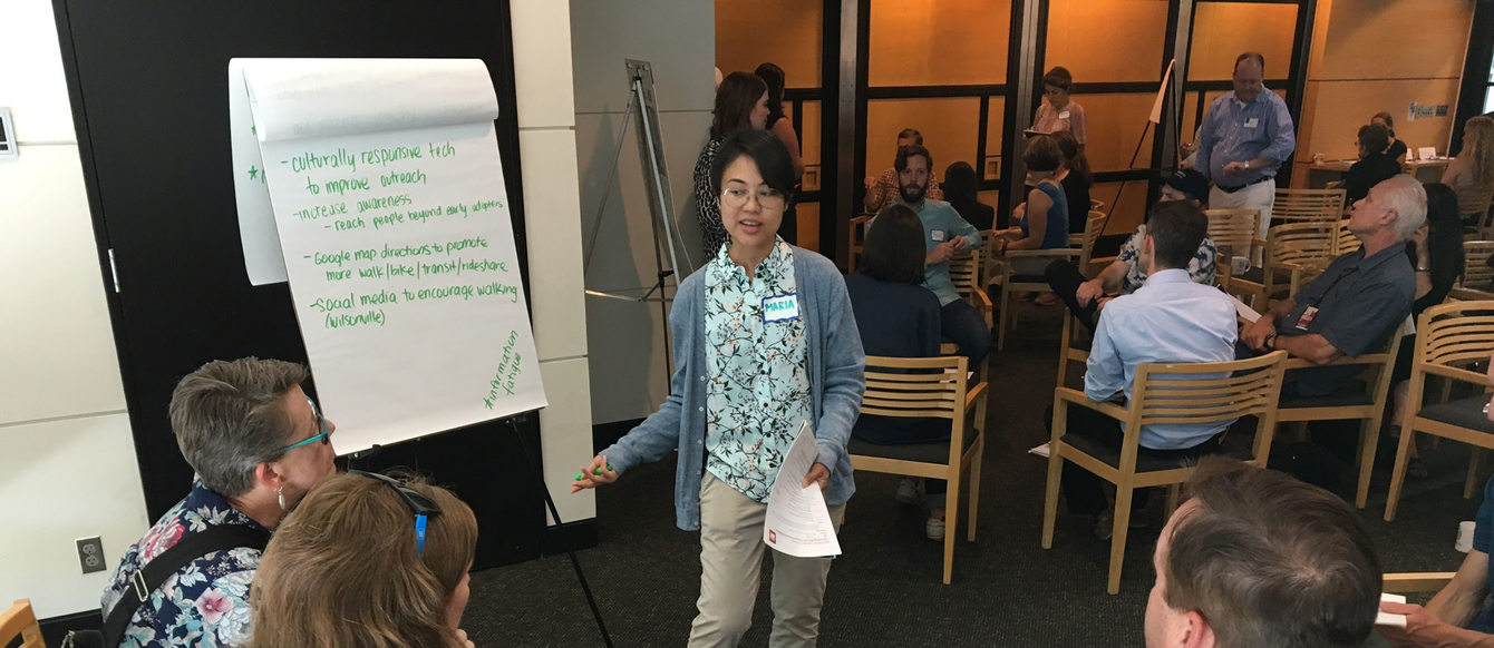 woman speaking to people and writing comments on a flipchart during a meeting in Metro Regional Center