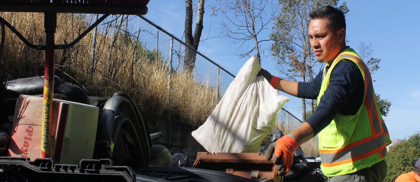 Photo of RID Patrol crew supervisor Juan Garcia loading truck with garbage