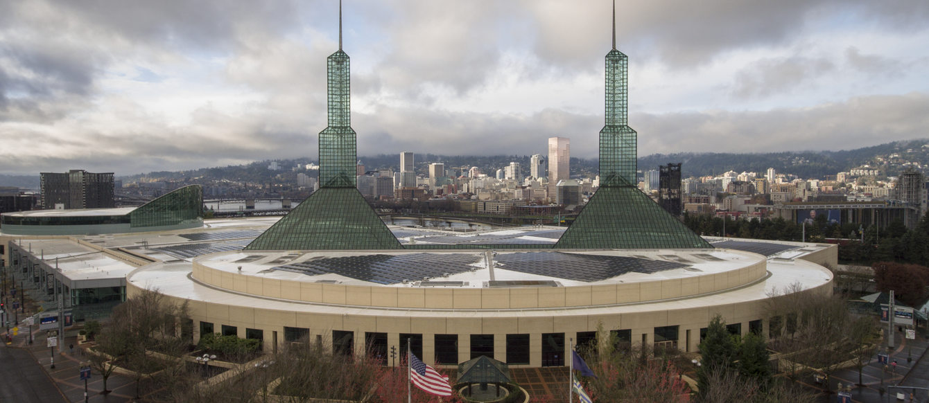 Oregon Convention Center in the daytime with the Portland skyline in the background
