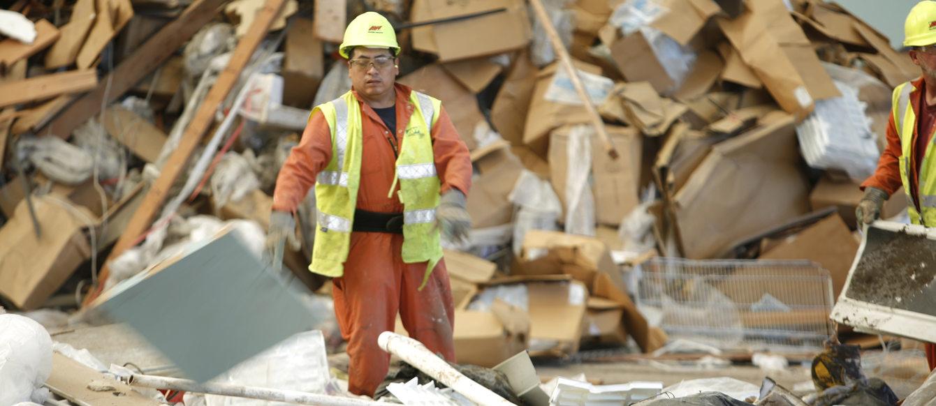 men sort through piles of trash