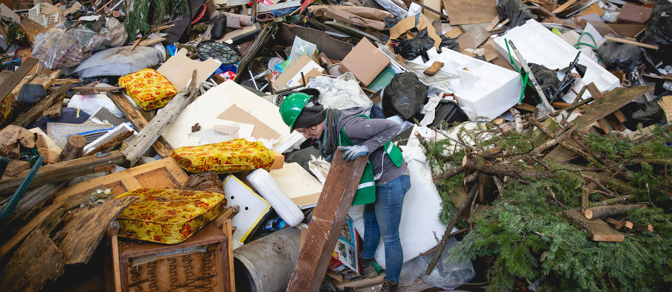 artist picks through giant pile of trash.