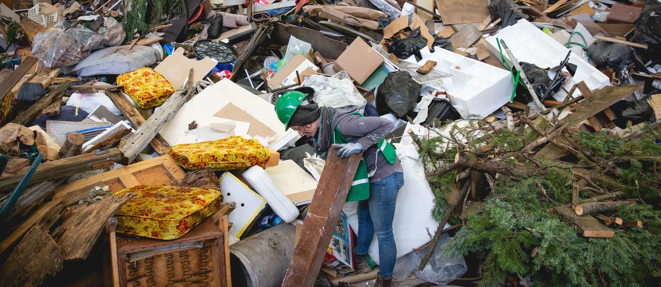artist picks through giant pile of trash.