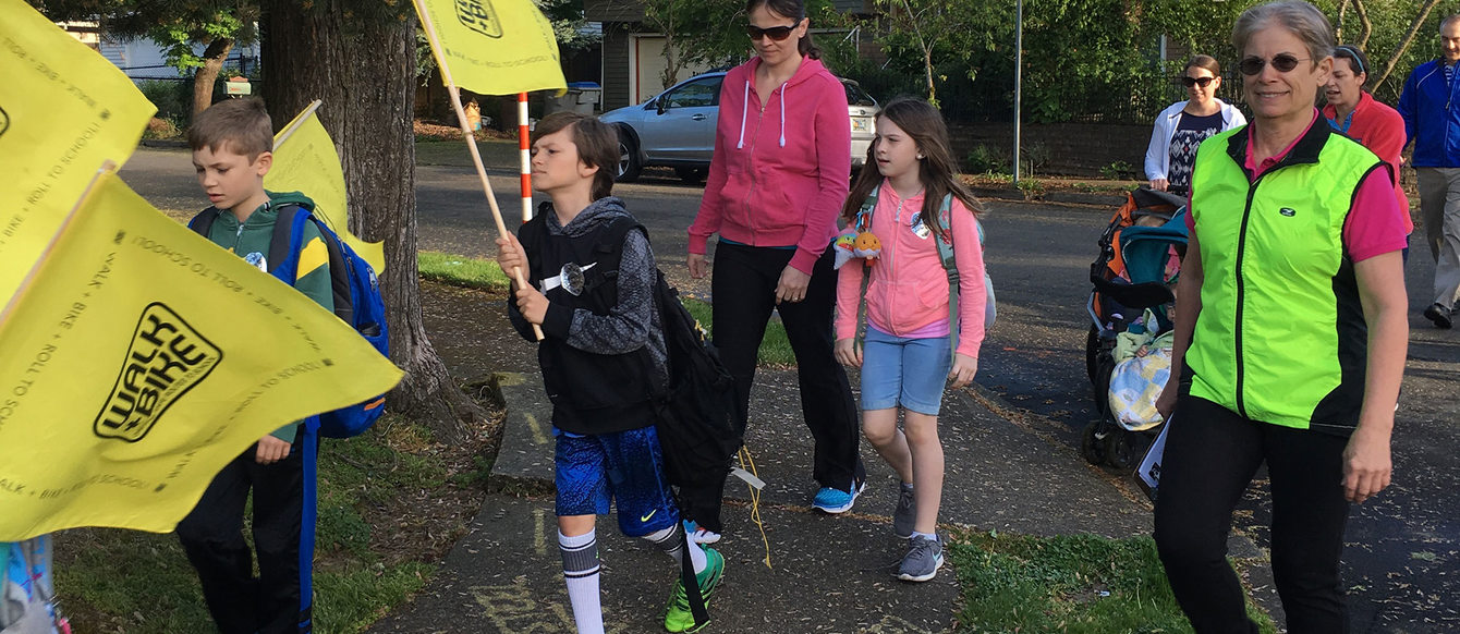 kids holding yellow flags walk on a sidewalk on their way to school with adults