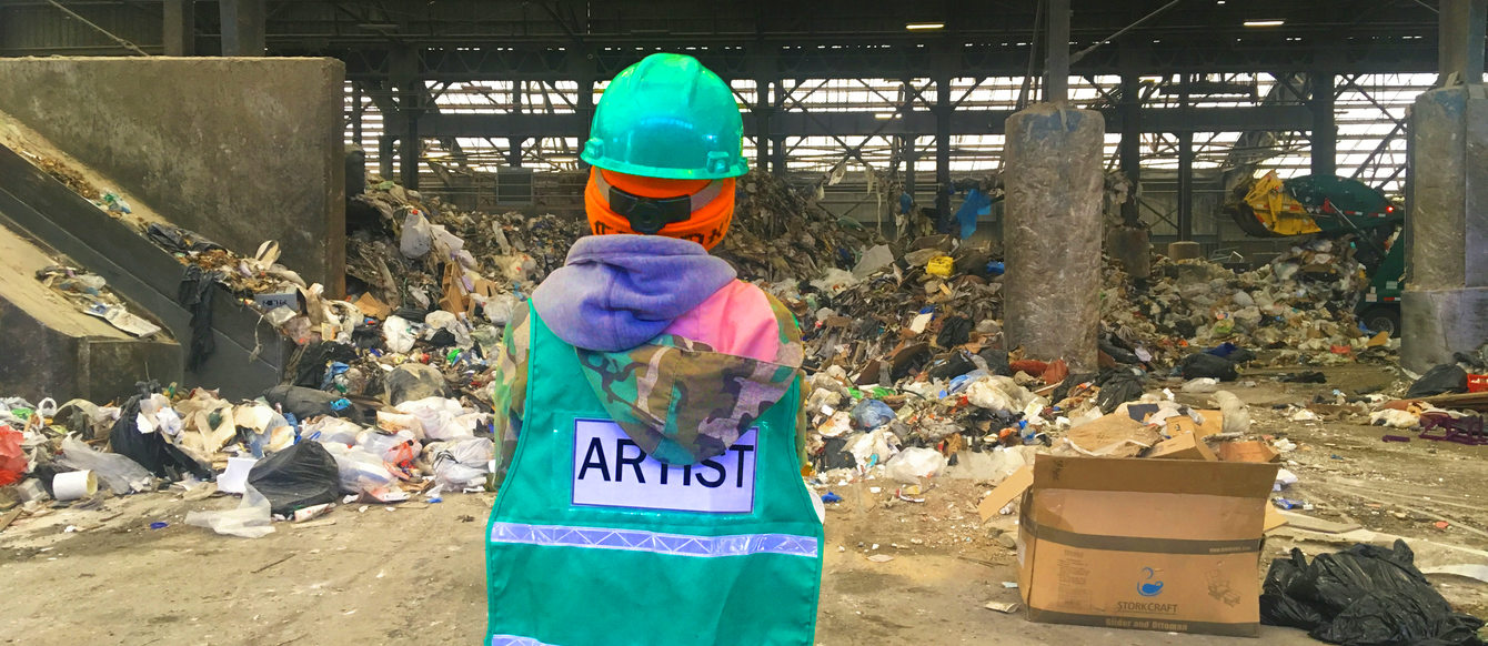 Artist in green safety vest stares at a giant pile of garbage