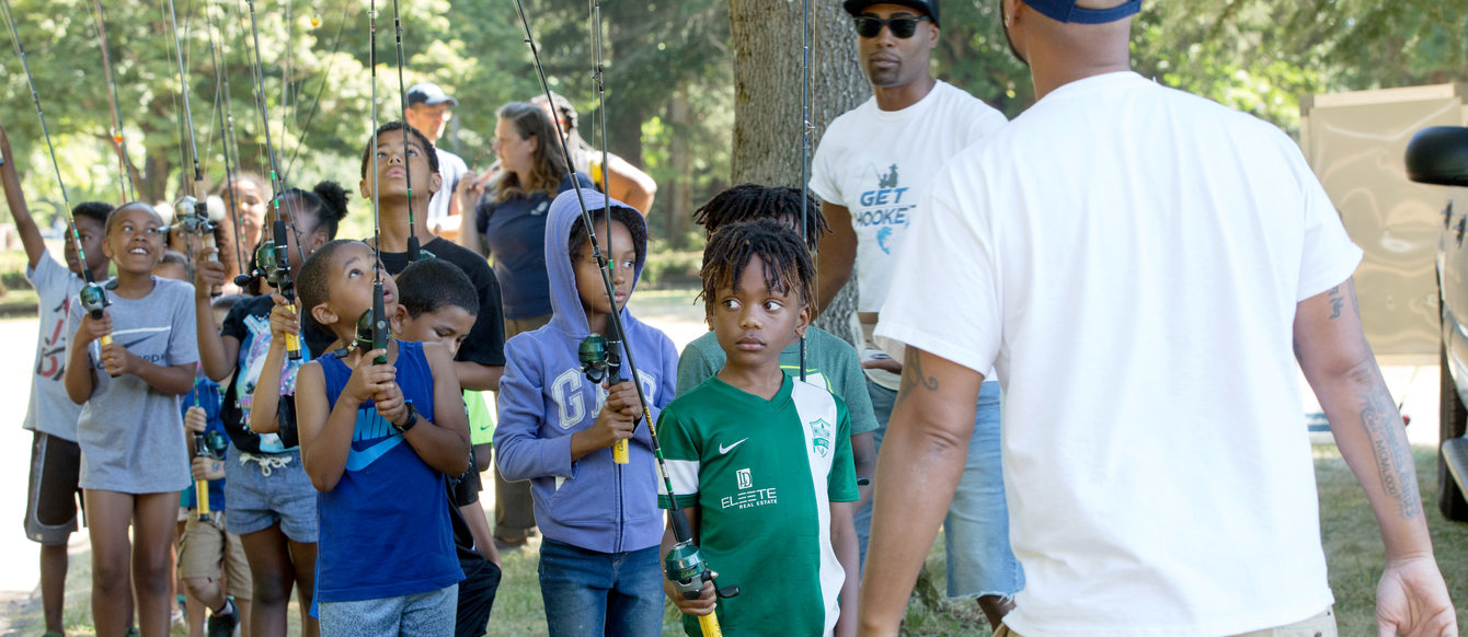 kids standing in line holding fishing pole at park