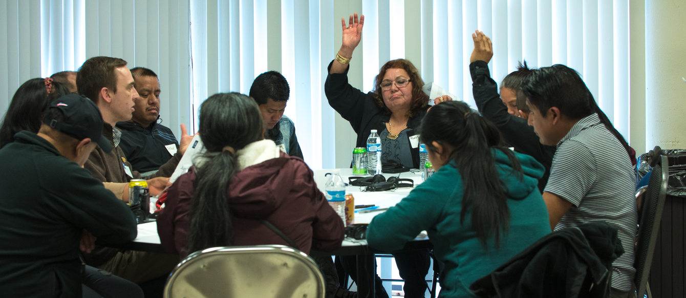 people raise their hands to vote on topics during a roundtable discussion at a community workshop